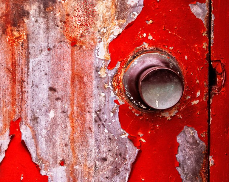 close up photograph of a red rusty door.