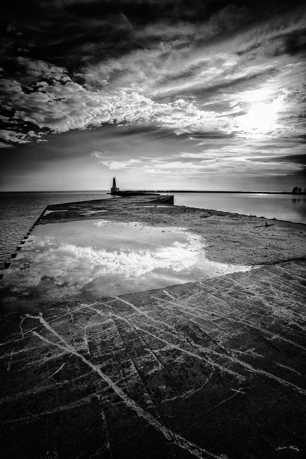 Black and White Photograph of Pier and sea, cloud reflections